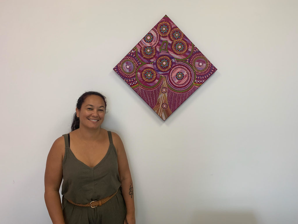 Photograph of Mim Cole and her artwork, the tree of life painting.